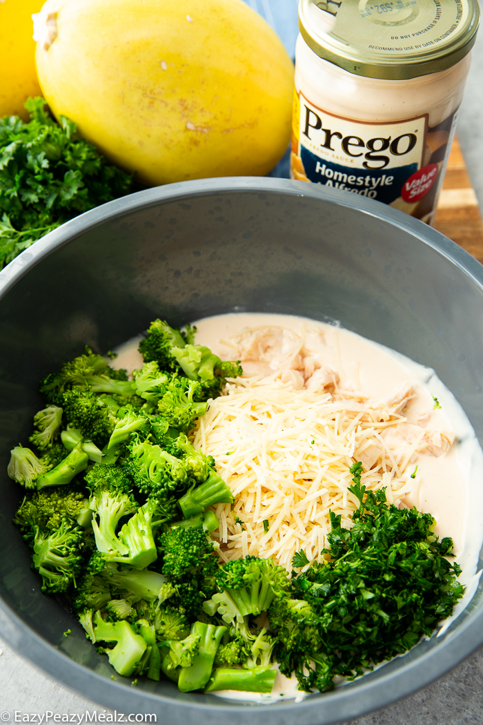 A gray bowl with the ingredients for spaghetti squash stuffed with broccoli chicken alfredo