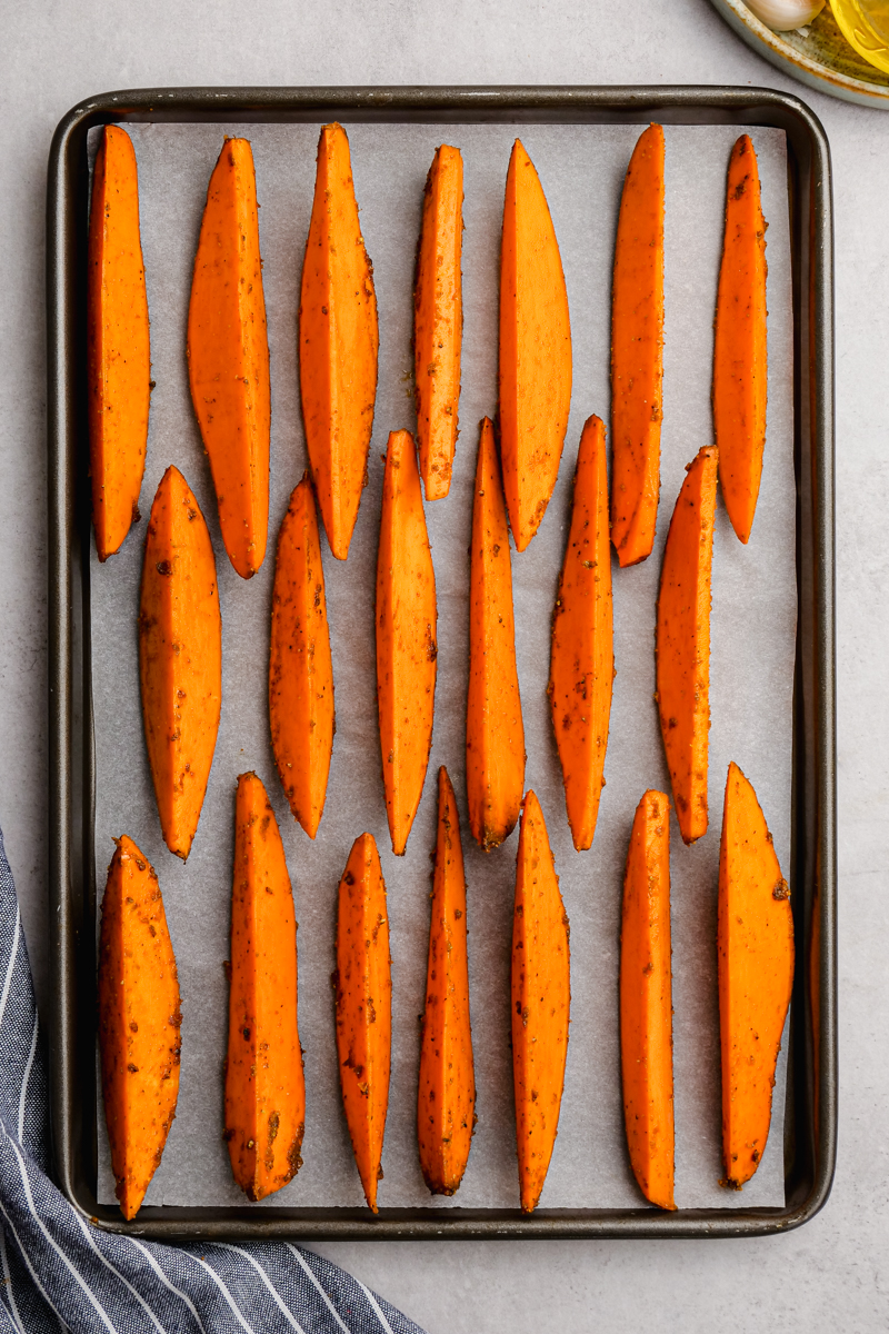 Sweet potatoes arranged skin side down on a baking sheet for being roasted