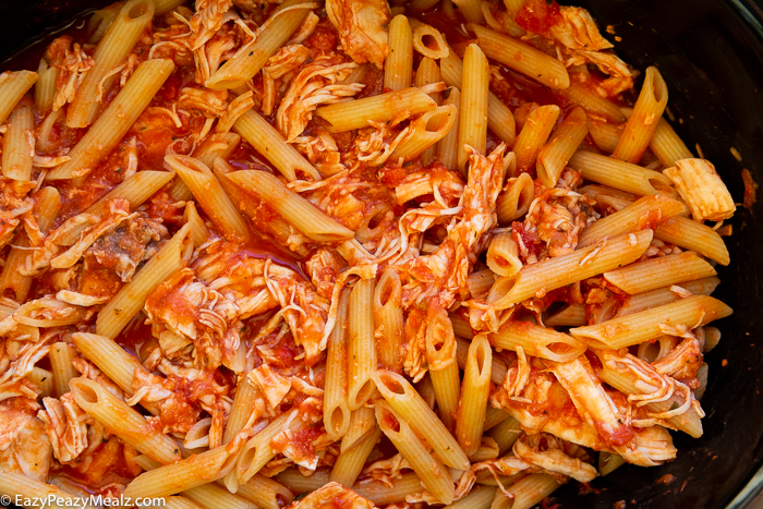 Penne with sauce, chicken and cheese in a slow cooker.