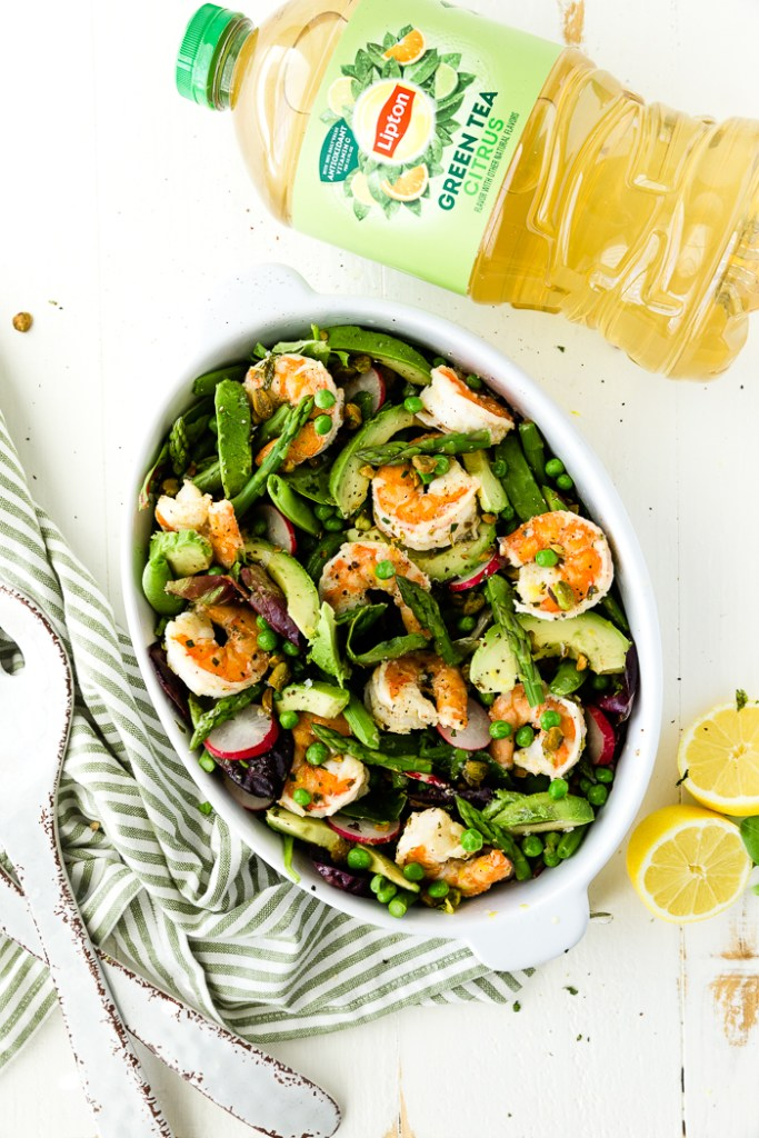 Citrus shrimp spring salad in a white bowl with lipton tea