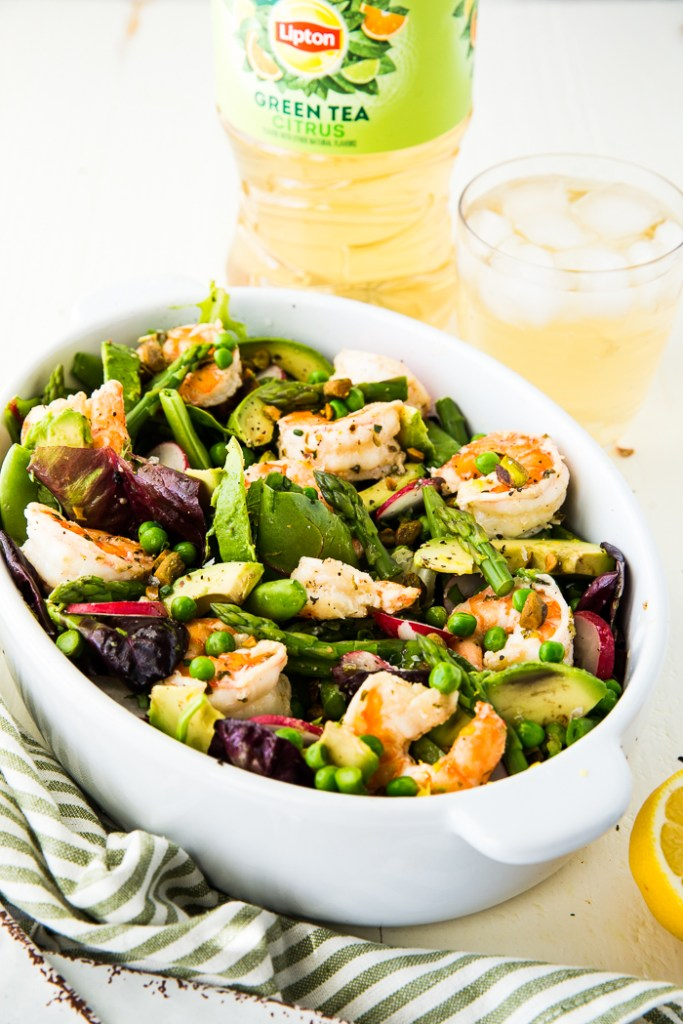 Citrus shrimp spring salad in a serving dish with iced tea