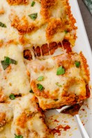 eggplant parmesan in white glass container on counter with spatula lifting out a square