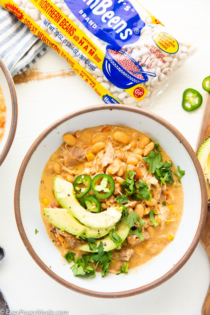 A bowl of white chicken chili topped with avocado, cilantro, and jalapeno.