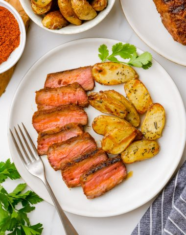 Sirloin steak with potatoes on a white plate
