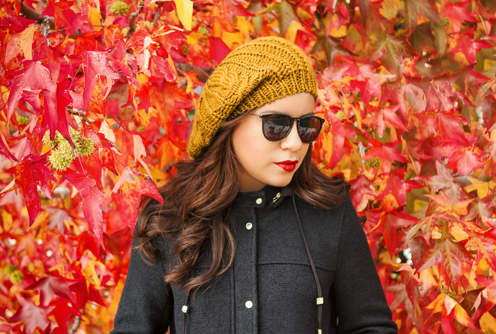 Woman wearing sunglasses and knit cap with leaves in background