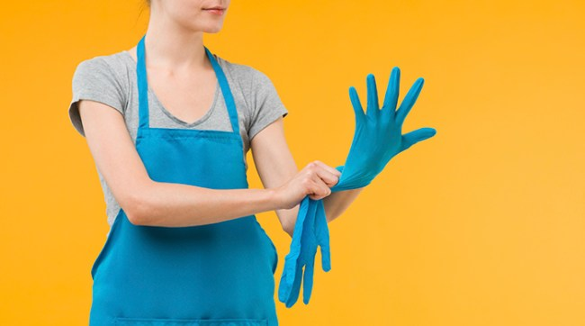 Woman Putting on Blue Kitchen Gloves