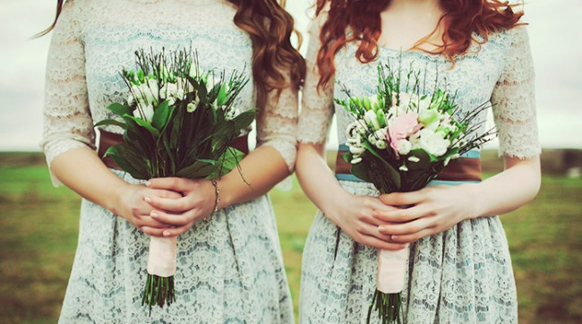 Two bridesmaids holding floral bouquets wearing matching dresses