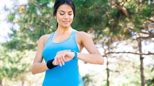 Happy sporty woman using smart watch