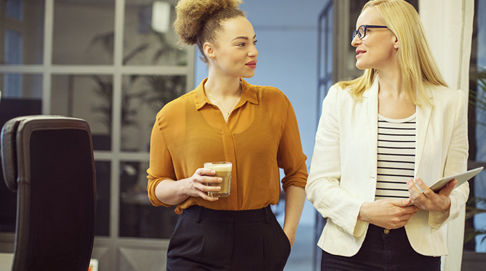 Two female colleagues discussing work while walking alongside each other in office