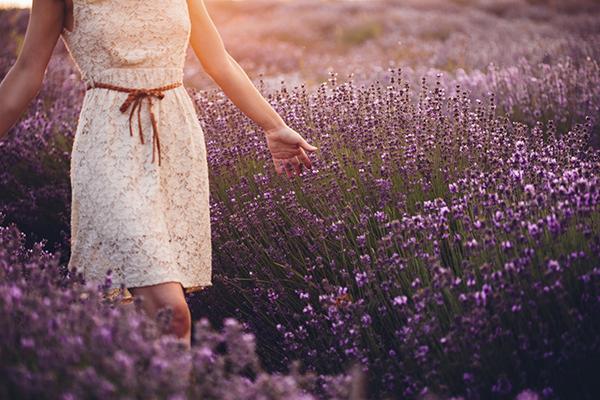 Woman in white dress walking through flowers