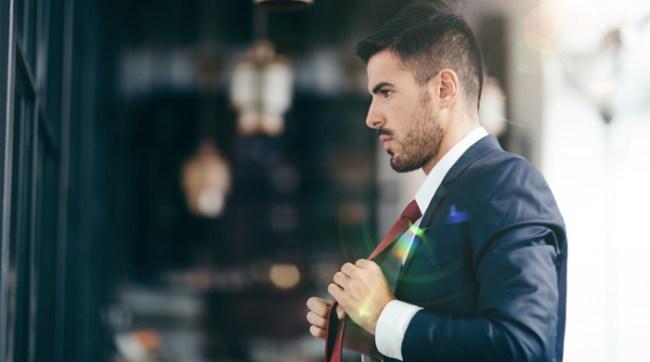 Man in suit adjusting his tie
