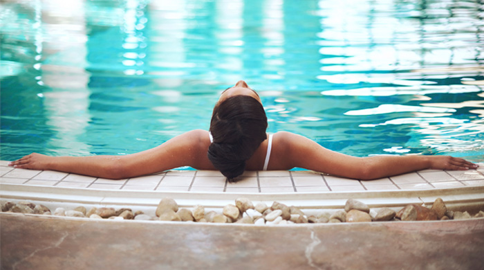Woman resting on the edge of a swimming pool spa