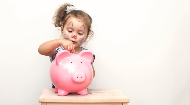 Little girl putting money into piggy bank