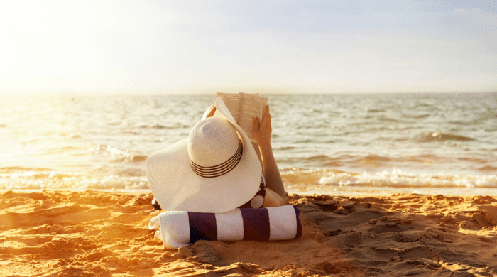 Woman in sun hat reading on the beach