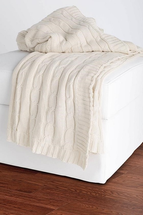 Cream throw blanket on bed