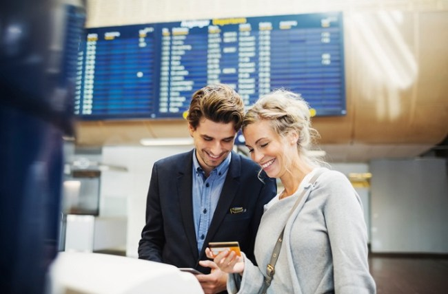 Couple at airport booking flight with credit card
