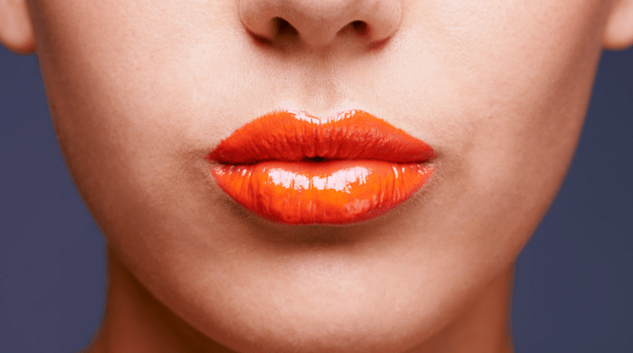 Woman wearing orange lip gloss