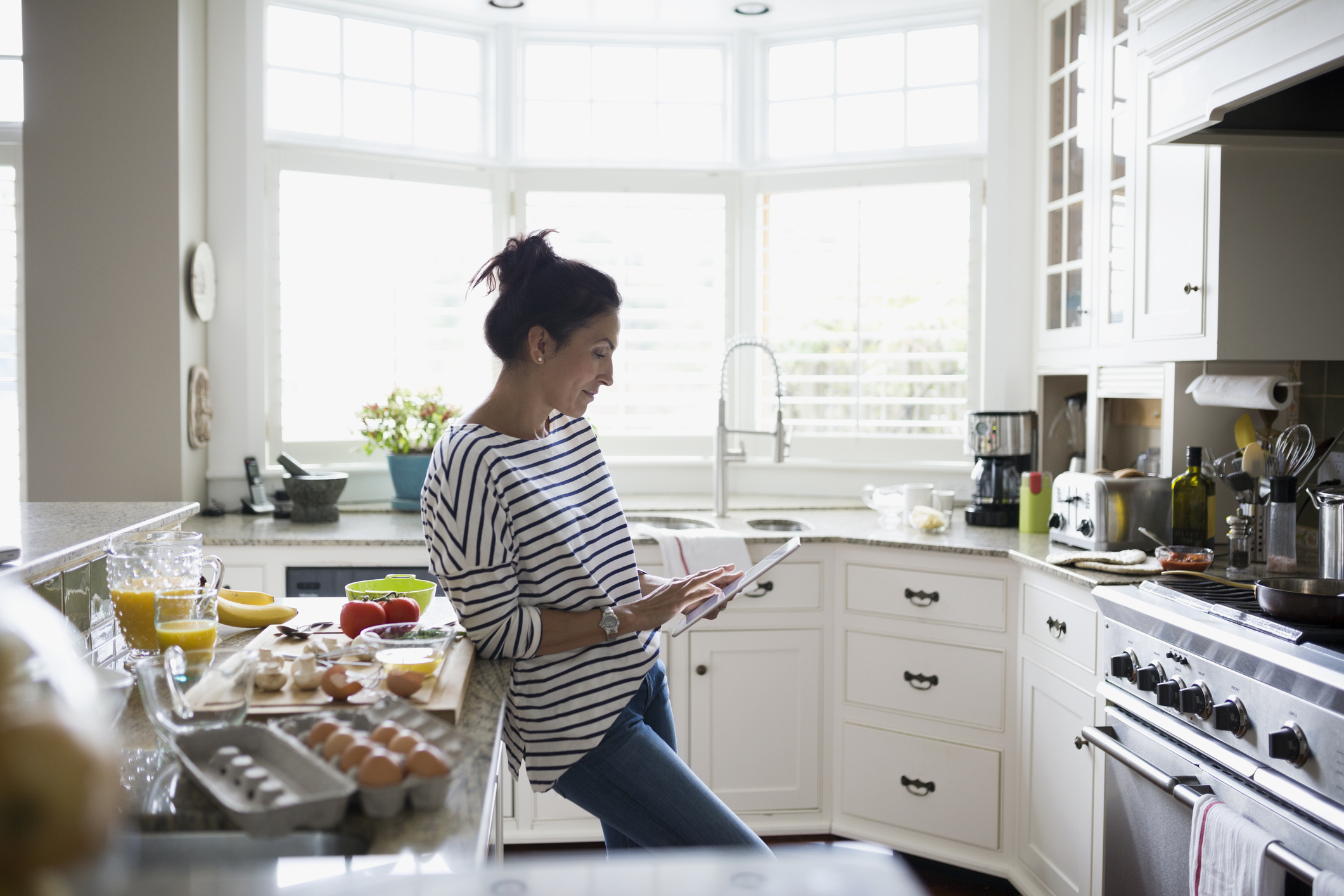 Woman cooking in kitchen looking up recipe on tablet