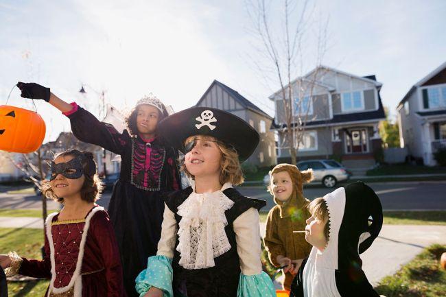 Kids in Halloween costumes trick or treating neighborhood