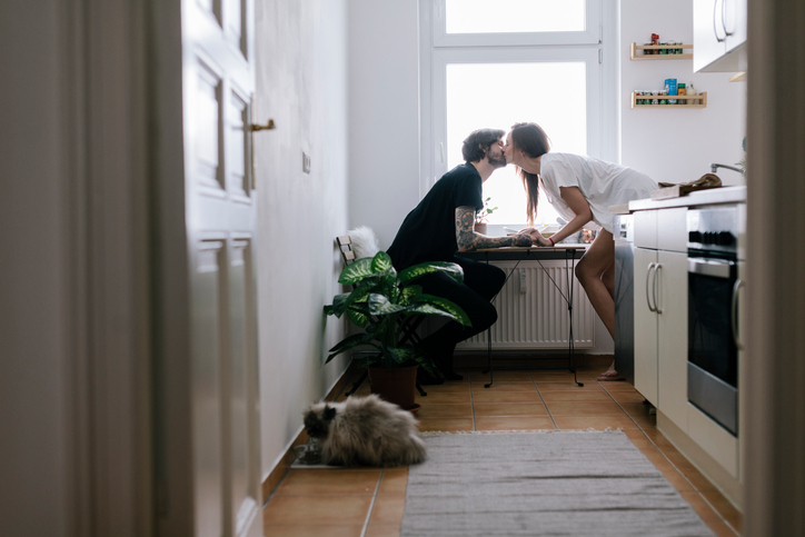 Young couple sitting in kitchen having a romantic moment