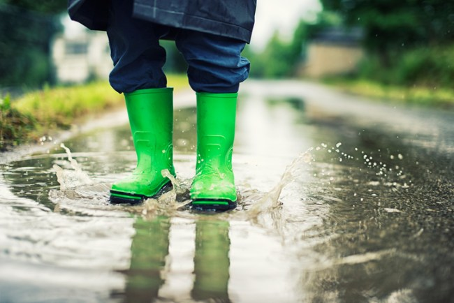 Closeup of kid's galoshes splashing in street puddle
