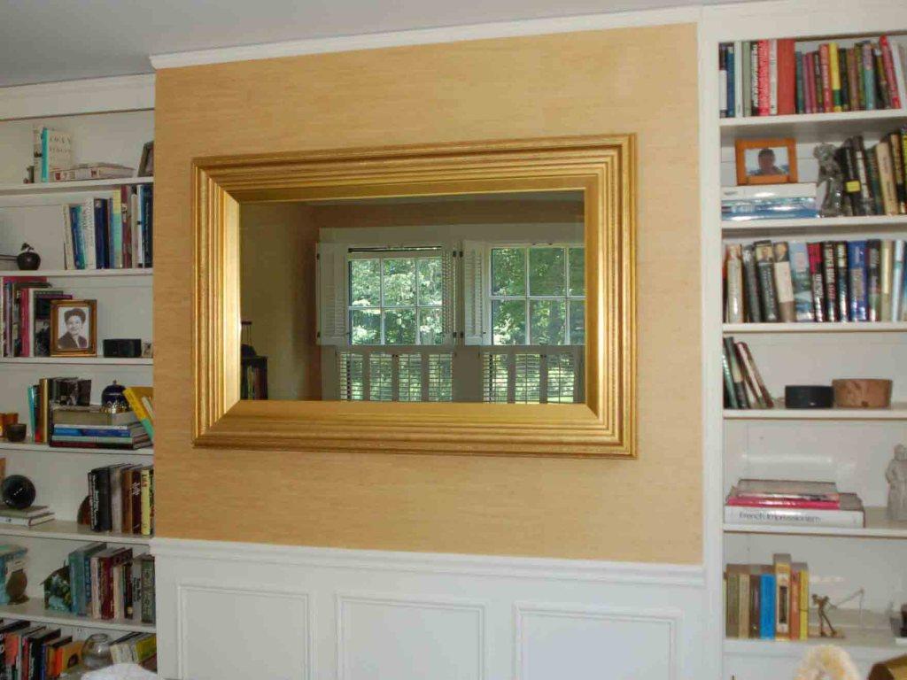 A flat screen tv / mirror framed in ornate gold