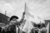"""A man waves a flag that reads, """"For peace with social justice."""""""