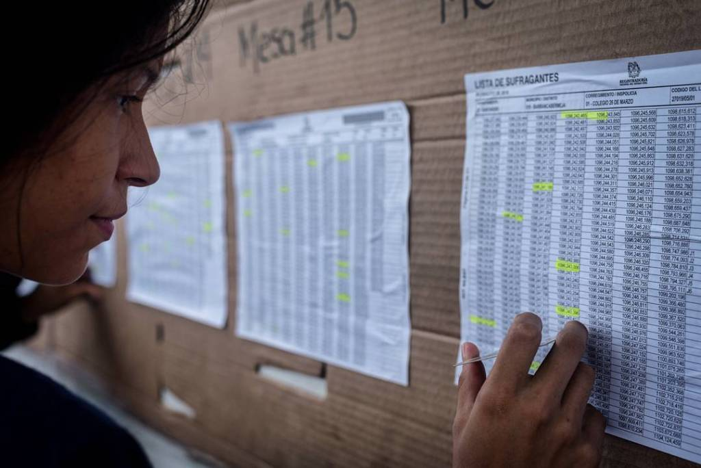 A woman looks for her identification number on a chart at a local voting station. (Photo: Caldwell Manners)