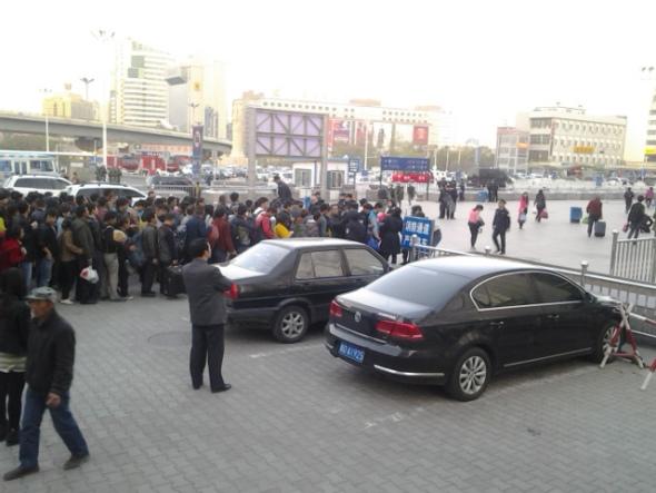 People wait at an entrance to the south railway station of Urumqi, capital of northwest China's Xinjiang Uygur Autonomous Region, after an explosion on April 30. People in the square in front of the station and nearby were evacuated immediately after the blast, and police cordoned off all entrances to the square of the station. [Photo by Gao Bo/China Daily]