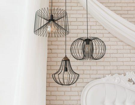 Wire black design ceiling luster hanging in bedroom. Loft interior details.