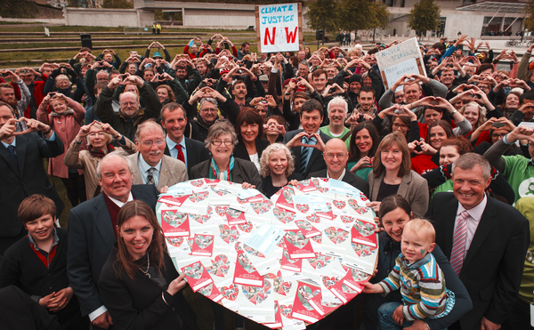 "PHOTOGRAPH FREE TO USE FOR FIRST USE PRINT AND ONLINE. EDINBURGH, UK - 27th May 2015:  Stop Climate Chaos Scotland (SCCS) hand over thousands of heart shaped postcards addressed to First Minister Nicola Sturgeon outside the Scottish Parliament as part of their ""For the Love of"" campaign.  The postcards feature messages which highlight things Scottish people care about that are threatened by climate change and let the Scottish Government know they want delivery on Scotland's climate commitments both at home and internationally. Pictured 3 year old Dougie Cook from Dunkeld hands over thousands of postcards to Climate Change Minister Aileen McLeod outside the Scottish Parliament. (Photograph: MAVERICK PHOTO AGENCY)"