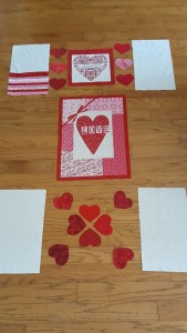 Panel pieces in rough layout for quilt