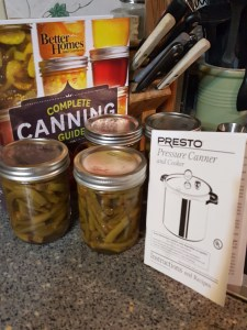 5 jars of green beans alongside recipe books