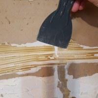 Plastic scraper taking off dried adhesive.