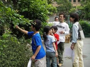 立体顕微鏡でのぞく虫などを探そうと校庭を駆け回り、指導員の井東さんを質問攻めにする子どもたち