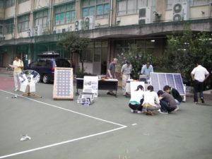 校庭にソーラーグッズを展示。大きな四角いものは太陽光発電パネル、一番左はソーラークッカーです。みんなが覗き込んでいるのは、太陽光で動くいろいろなソーラーグッズ。