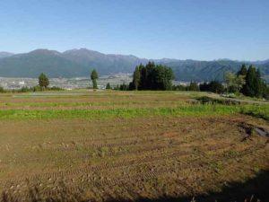すっかり雪が消えた山々を望む「イロハ田んぼ」。肥料まきが進んでいました。