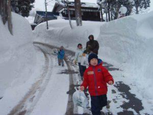 正月飾りを集めて回っている様子。子どもたちが持っているビニル袋の中には、しめ縄やお札などがたくさん。