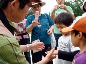「トンボの羽を挟んで持つように」と講師から教わる地元の子どもたち。