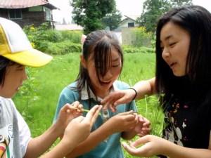 カナヘビを捕まえた村の子どもたち。