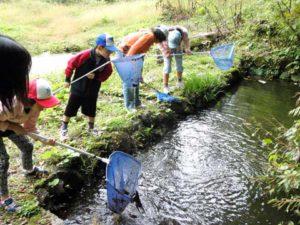 池の泥をどんどんすくう子どもたち