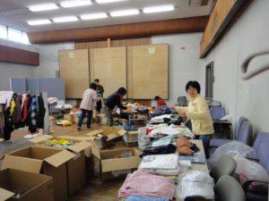 塩沢市民センターの講堂いっぱいに広げられた衣類の支援物資