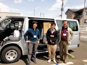 福島・宮城へ出発する直前の高野、大前と日熊恵一さん。ワゴン車には隙間なく、ランドセルや文具、食料、衣料などが積み込まれました