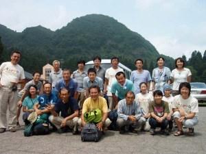 集った参加者のみなさん。背景は栃窪集落のシンボルになっている樽山(736m)