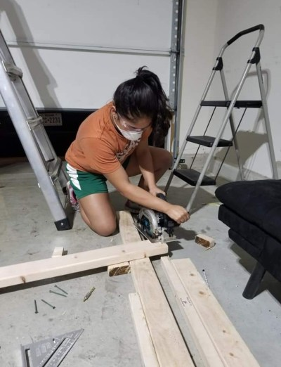 Sophia cutting lumber for a self-designed and built storage unit for her family's garage.