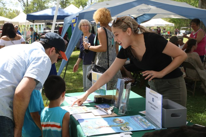 woman at Defenders of Wildlife booth giving info to man and child