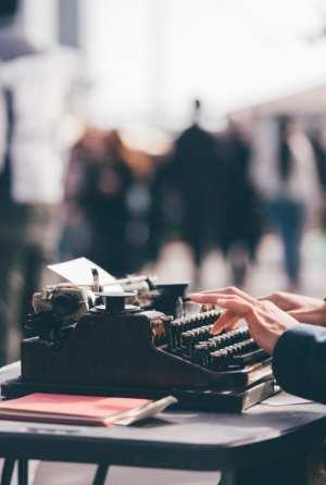 Une personne utilise une machine à écrire en public.