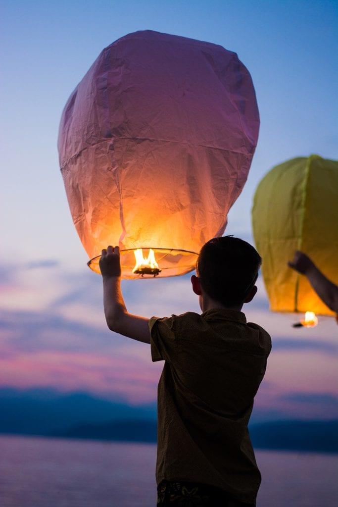Un enfant tient une lanterne volante dans le crépuscule
