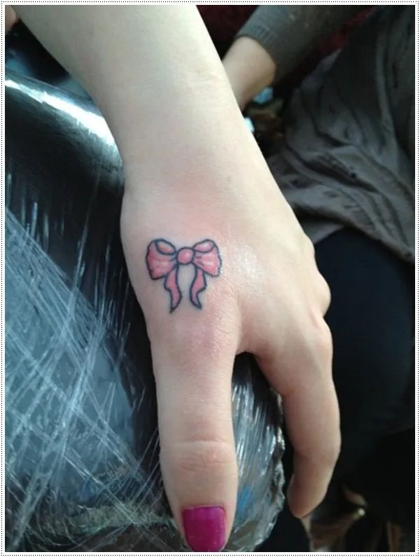 A colorful bow hand tattoo can definitely make a statement.