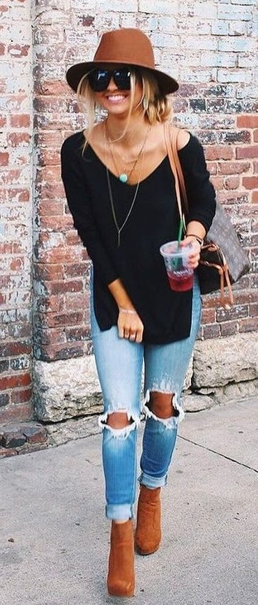 women's black off-shoulder long-sleeve shirt, blue distressed denim jeans, and brown leather boots